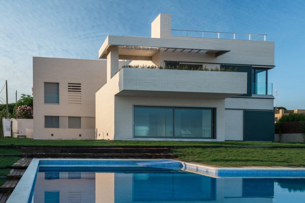 Fachada y piscina de chalet unifamiliar junto a la playa. Construido por iLuxenio en Sanlucar de Barrameda, Cádiz