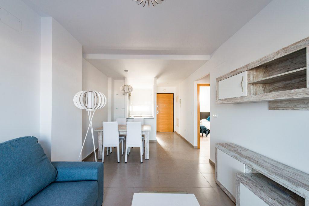 Toma amplia con un gran angular de 16mm. Se ve la amplitud de un salón, diáfano que conecta con comedor y cocina. También se ve la entrada y habitación principal.