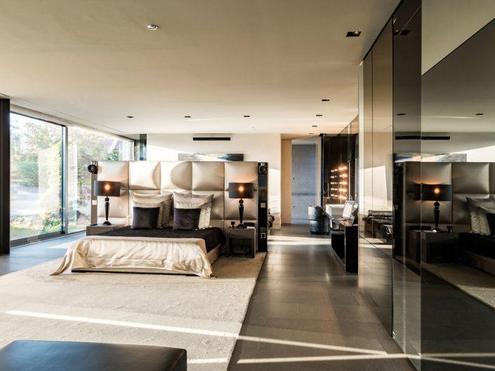 Dormitorio con grandes ventanales con luz de atardecer. Jacuzzi y baño en suit