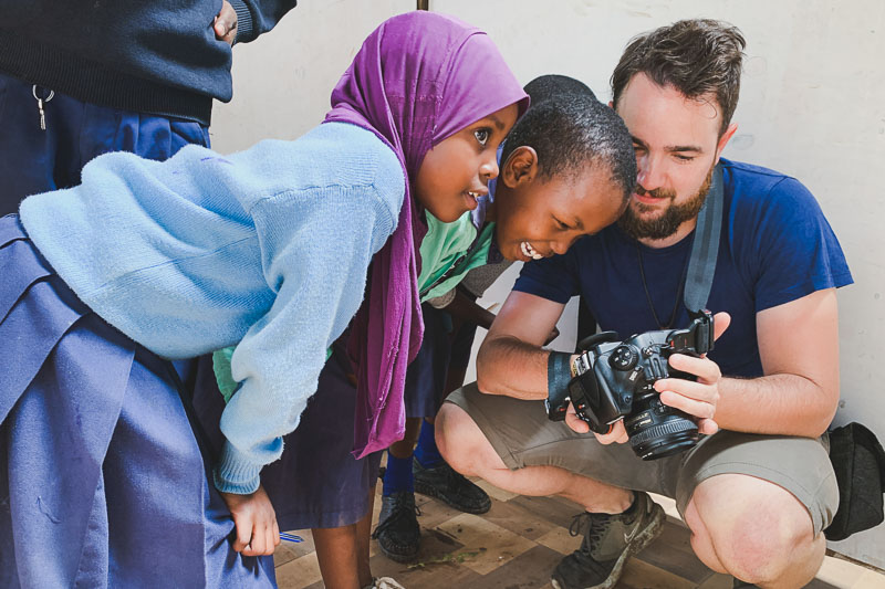 Fotógrafo cooperante en Tanzania enseña una imagen a un par de niñas tanzanas